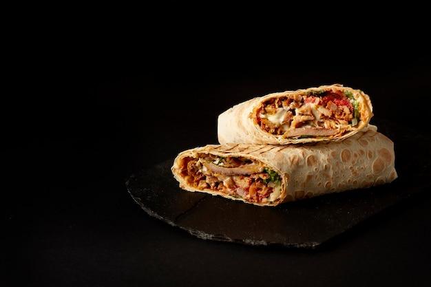 Shawarma, bułka w lawaszu, mięso z grilla, z warzywami, kanapka, krojona na czarnym stole, pozioma, kopia