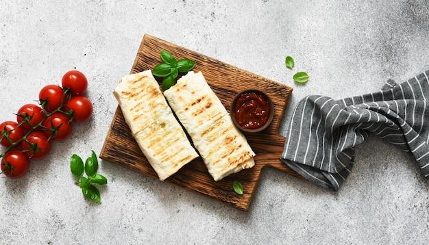 Shawarma faszerowana mięsem i warzywami na drewnianej desce na konkretnym tle. widok z góry.