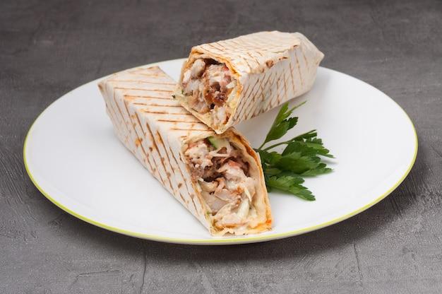 Shawarma lub kebab doner z kurczakiem na białym talerzu