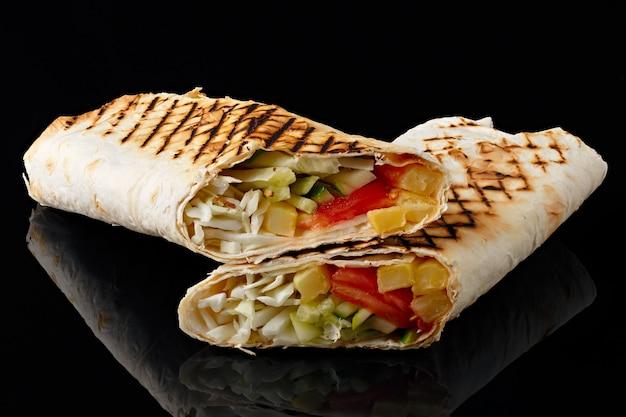 Shawarma w chlebie pita jest cięta i leży na czarnym odblaskowym tle