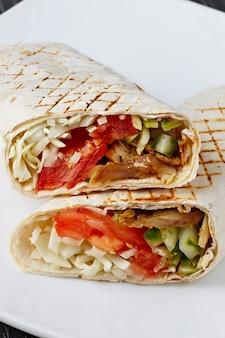 Shawarma w chlebie pita jest krojona i leży na białym talerzu