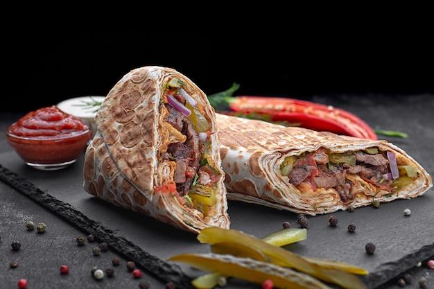 Shawarma z cielęciną, z sosem, cebulą, piklami, ziołami i ostrą papryką, na łupku, na ciemnym tle betonu