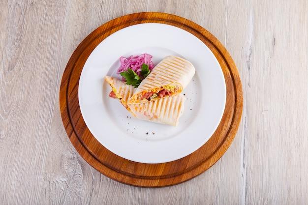 Shawarma z marynowaną cebulą z kurczaka na białym talerzu