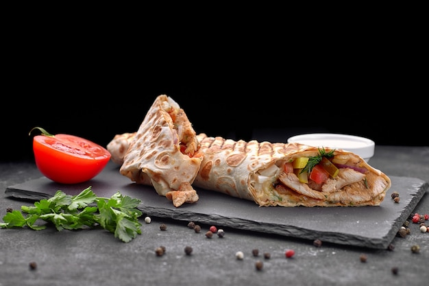 Shawarma z mięsem, cutaway, z sosem, pomidorami, serem, ziołami i czosnkiem, na czarnym łupku