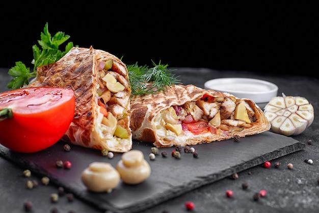 Shawarma z mięsem drobiowym, z sosem, cebulą, ogórkami, pomidorem, czosnkiem, pieczarkami i ziołami, na łupku, na ciemnym tle betonu