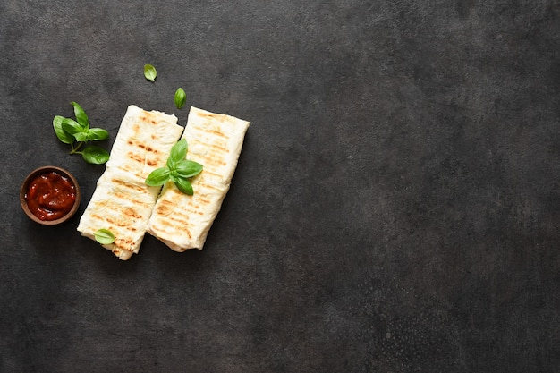 Shawarma z mięsem i warzywami na desce na czarnym tle, widok z góry.