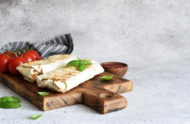 Shawarma z mięsem i warzywami na drewnianej desce na stole w kuchni. kawałek shawarmy.