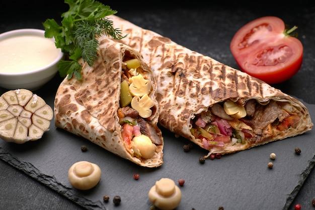 Shawarma z mięsem, z sosem, cebulą, piklami, pomidorem, czosnkiem, pieczarkami i ziołami, na łupku, na ciemnym tle betonu
