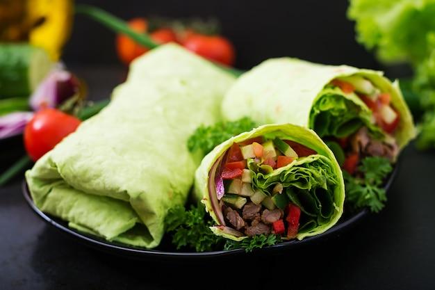 Shawarma z soczystej wołowiny, sałaty, pomidorów, ogórków, papryki i cebuli w chlebie pita ze szpinakiem. menu dietetyczne