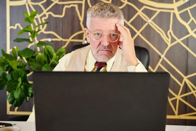 Shoked starszy biznesmen czytanie raportu lub umowy na ekranie laptopa w nowoczesnym biurze