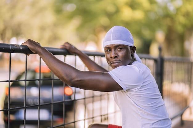 Shot of african-american mężczyzna w białej koszuli stwarzających w parku