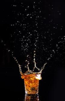 Shot whisky z odrobiną na czarnej powierzchni, brandy w szklance