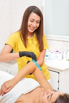 Shugaring: beauty concept - kosmetyczka w żółtej koszulce, uśmiechnięta, usuwa włosy z dłoni klientki