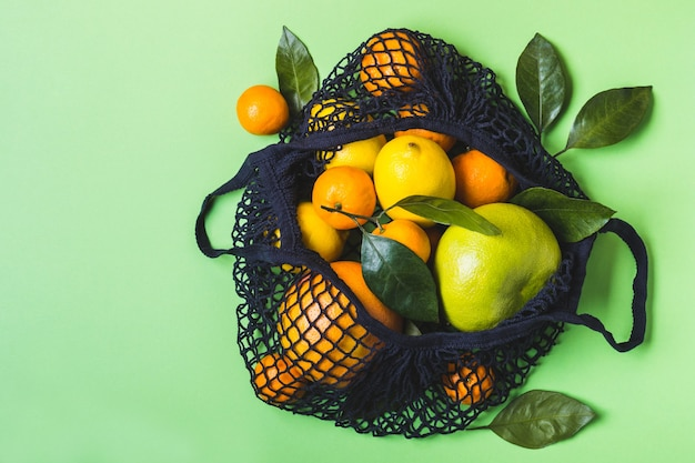Siateczkowa torba tekstylna pełna kolorowych owoców. zdrowa żywność i koncepcja zero odpadów.