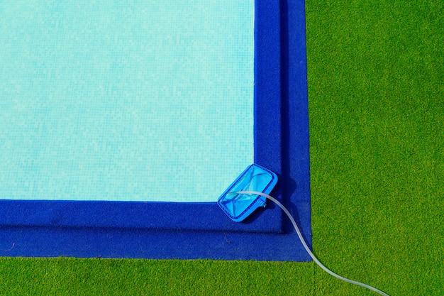 Siatka czyszcząca z góry na brzegu basenu to zielona i niebieska sztuczna trawa.