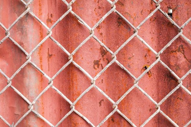 Siatka druciana i czerwone tło ogrodzenia falistego