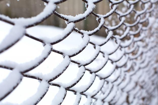 Siatka ogrodzeniowa zmiażdżona przez śnieg.
