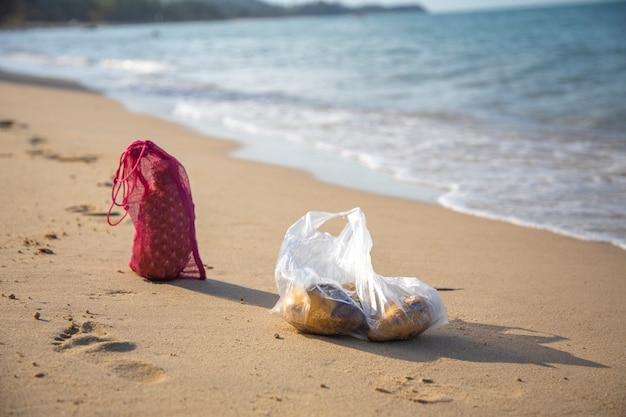 Siatkowa torba na zakupy i plastikowa torba leżą na piaszczystej plaży nad morzem w słoneczny dzień. ekologia koncepcji oceanów