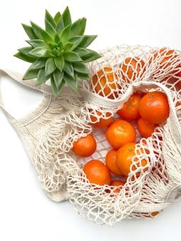 Siatkowa torba świeżych pomarańczy zdrowych owoców cytrusowych na białym tle