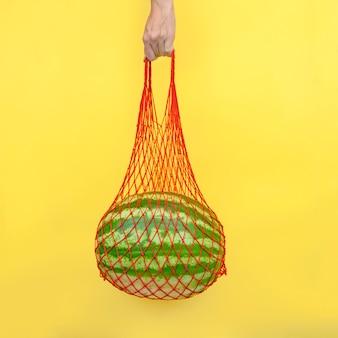 Siatkowa torba z arbuzem w ręku na żółtym tle