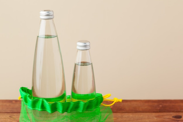Siatkowe torby z szklaną butelką wody wielokrotnego użytku.