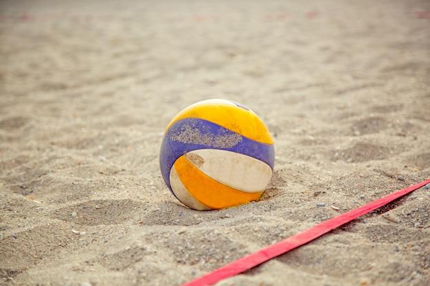Siatkówka plażowa. gemowa piłka pod światłem słonecznym i niebieskim niebem. siatkówka w piasku na plaży
