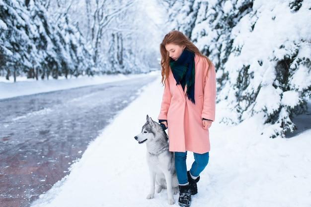 Siberian husky siedzi w pobliżu młodej kobiety