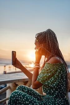Sideview strzał kobiety z dredami w dresswith słuchawki i telefon na plaży.