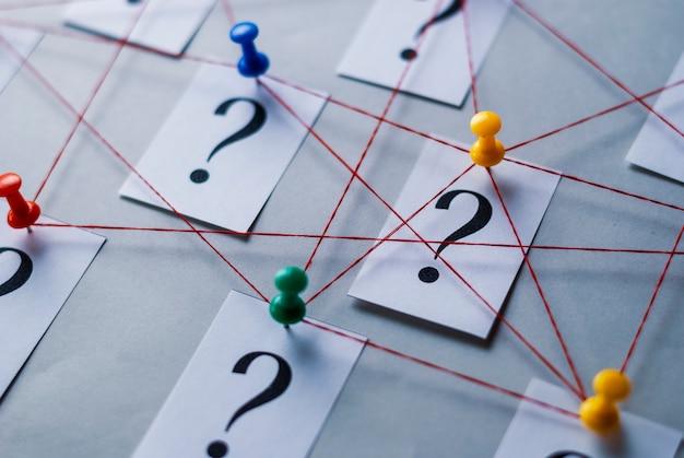 Sieć drukowanych znaków zapytania na białych kartach