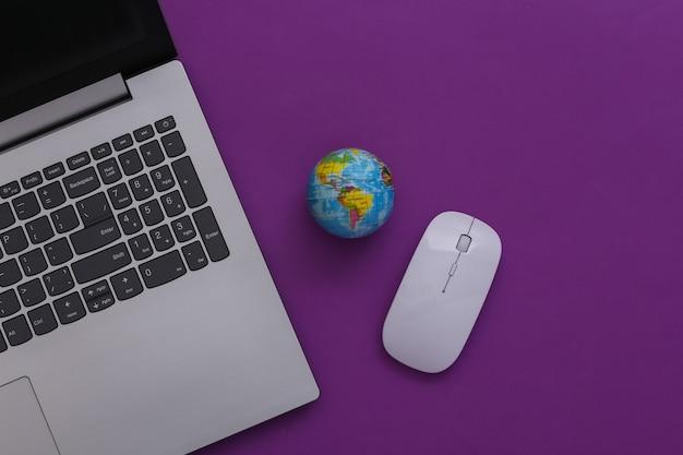 Sieć globalna. laptop z myszką pc i kulą ziemską na fioletowym tle. widok z góry. płaskie ułożenie