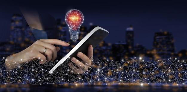 Sieć jasny pomysł z żarówką. ręka dotykowy biały tablet z cyfrowym hologramem żarówka znak na ciemnym tle niewyraźne miasta. pomysły innowacyjne technologie i kreatywność.