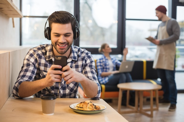 Sieć społecznościowa. radosny miły młody człowiek siedzi przy stole i używa swojego smartfona, jednocześnie ciesząc się nowoczesną technologią