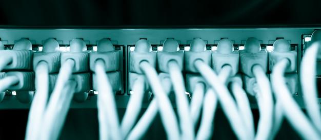 Sieciowe kable ethernetowe łączą się ze stelażem serwerowym w centrum danych uniwersytetu