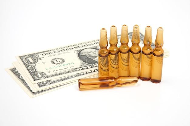 Siedem medycznych ampułek szklanych do wstrzykiwań na tle banknotów dolarowych