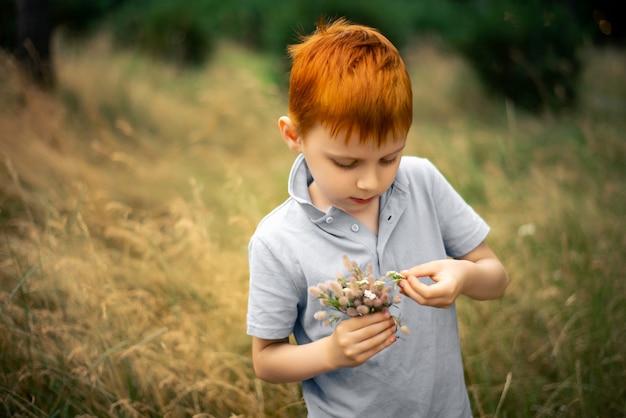 Siedmioletni chłopiec z rudymi włosami i bukietem polnych kwiatów latem