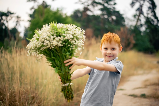 Siedmioletni chłopiec z rudymi włosami i dużym bukietem polnych kwiatów latem