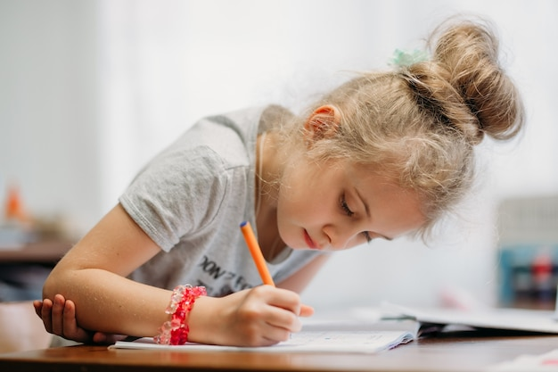 Siedmioletnia dziewczynka siedzi w domu przy stole i pisze w zeszycie, wykonując zadanie do nauki lub powtarzając lekcje.