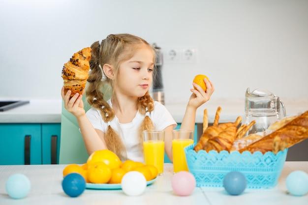 Siedmioletnia dziewczynka, ubrana w białą koszulkę, siedzi przy kuchennym stole. zawiera mandarynki i świeżo upieczony croissant z czekoladą
