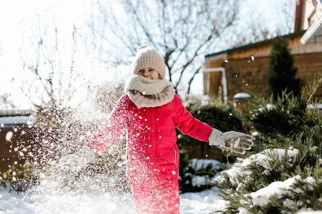 Siedmioletnia ładna dziewczyna w zimowe ubrania bawiące się śniegiem na podwórku domu w słoneczny zimowy dzień.