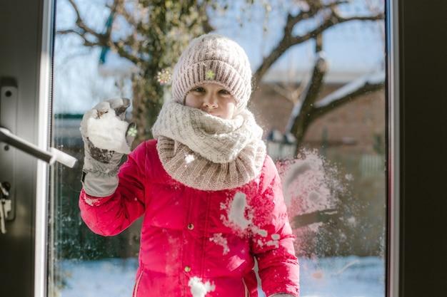 Siedmioletnia śliczna dziewczyna w zimowych ubraniach stoi przed drzwiami, na ulicy ze śniegiem w dłoniach i patrząc do domu z uśmiechem.