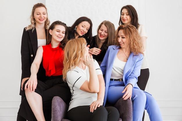 Siedmiu różnych kolegów, współpracowników stoi i siedzi razem w biurze, obejmuje się.