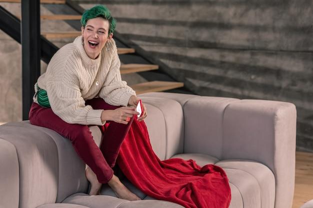 Siedząc i śmiejąc się. zabawna zielonowłosa kobieta siedzi na kanapie i śmieje się po telefonie od koleżanki