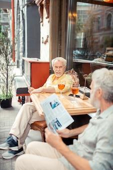 Siedząc na zewnątrz stołówki. siwowłosi emeryci spotykający się w weekend na zewnątrz stołówki