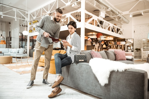 Siedząc ze smartfonem. brodaty mężczyzna w szarym swetrze pokazuje zainteresowaną próbkę, podczas gdy jego żona siedzi ze skrzyżowanymi nogami