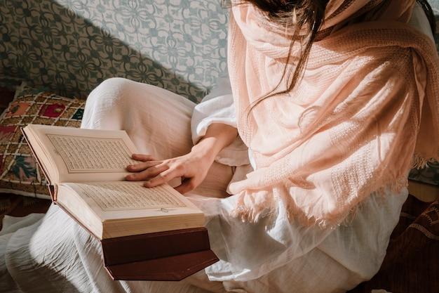 Siedząca kobieta czytająca w koranie