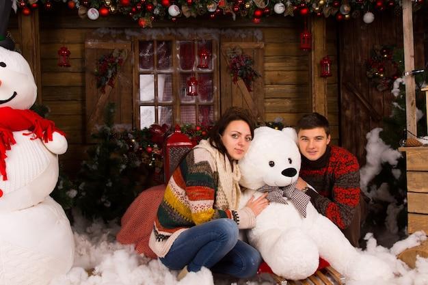 Siedząca młoda para w zimowych strojach przytulająca białego misia zimowego w drewnianym domu ozdobionym dużym bałwanem i różnymi dekoracjami świątecznymi.