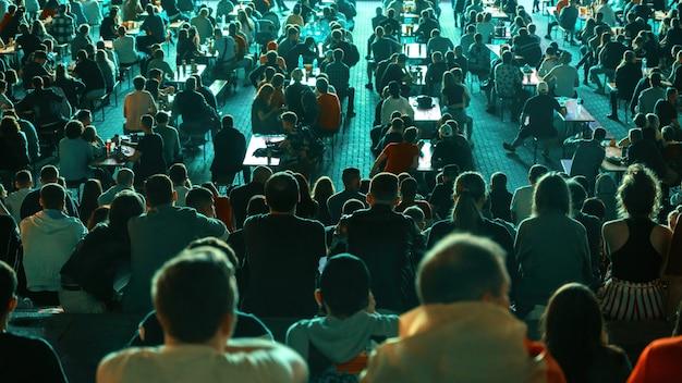 Siedzące osoby oglądające piłkę nożną w miejscu publicznym w nocy