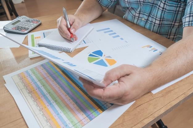 Siedzący biały człowiek rozliczający się z kalkulatorem i przeglądający przepływy pieniężne i pieniężne, prognozy i faktury. praca koncepcyjna w domu, rachunki rozliczeniowe, ekonomia domu.