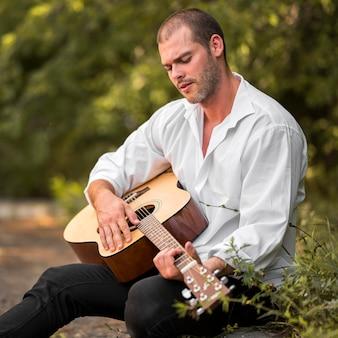 Siedzący mężczyzna gra na gitarze w naturze