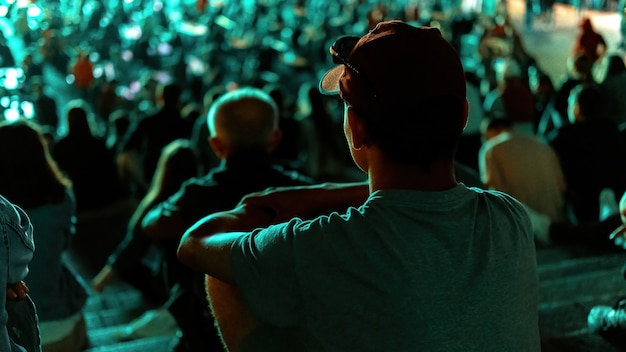 Siedzący mężczyzna oglądający piłkę nożną w miejscu publicznym w nocy